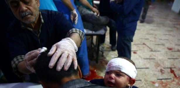 Bebê ferido chora no colo de homem após bombardeio perto de Damasco na Síria