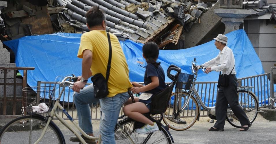 18.jun.2018 - Pessoas olham para casa destruída após o terremoto que atingiu a cidade de Ibaraki, no norte de Osaka, no Japão