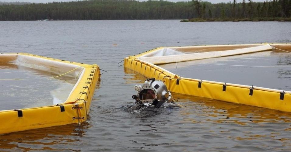 Mergulhador coloca sacos de areia debaixo d'água para proteger o local onde será realizado o experimento