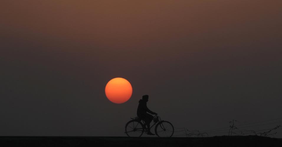 31.dez.2018 - Homem anda de bicicleta durante último pôr do sol de 2018 em Lahore, no Paquistão