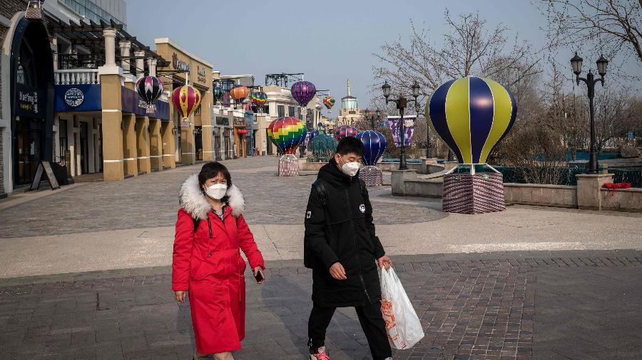 25.fev.2020 - Pessoas usam máscaras como medida preventiva contra o novo coronavírus ao andar em shopping de Pequim - Nicolas Asfouri/AFP