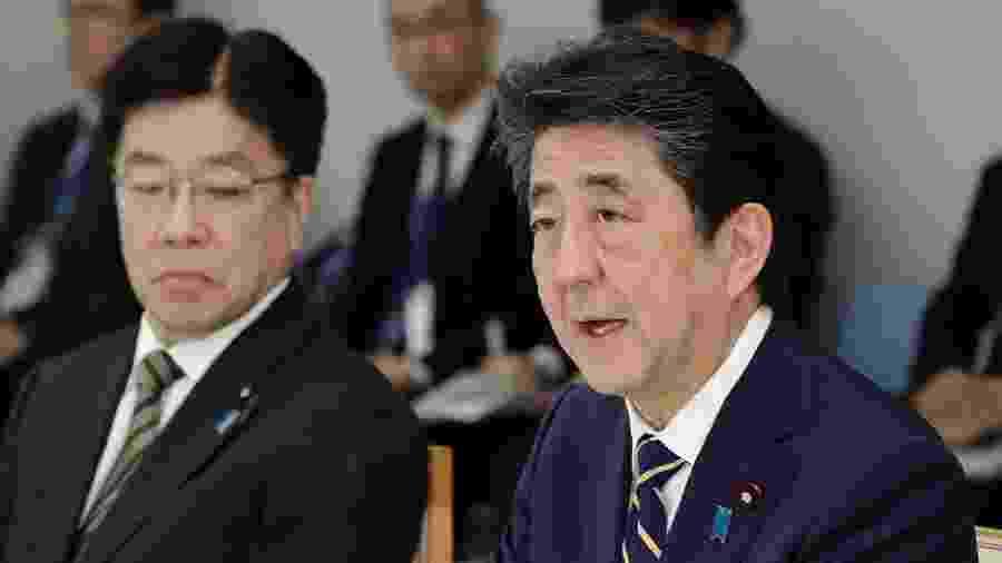 Shinzo Abe (dir.) e ministro da Saúde japonês, Katsunobu Kato (esq.), participam de reunião para conter a disseminação do coronavírus no país - STR/Jiji Press/AFP