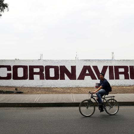 Uma pintura escrita coronavírus é vista em um muro enquanto um homem passa de bicicleta na Cidade do México - CARLOS JASSO/REUTERS