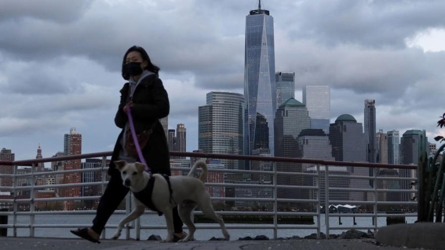 De máscara, mulher passeia com seu cachorro em Jersey City, Nova Jersey; ao fundo, está o World Trade Center, em Nova York - Gary Hershorn/Getty Images - 27.abr.2020
