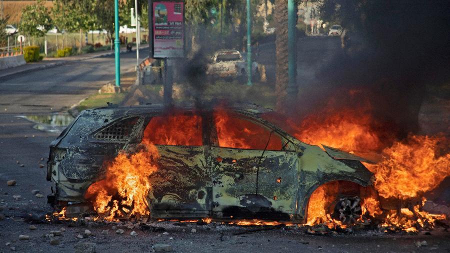 Um carro da polícia israelense queima após uma manifestação árabe israelense após o funeral de Mousa Hassouna na cidade central de Lod, perto de Tel Aviv - AFP