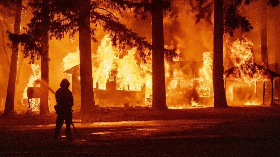 Bombeiro tenta apagar chamas de incêndio florestal em Indian Falls, na Califórnia (EUA) - Josh Edelson/AFP