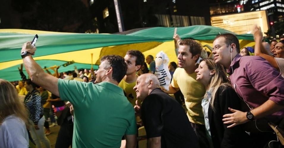 16.mar.2016 - Manifestantes fazem selfie ao lado de bandeira com as cores do Brasil durante protesto na avenida Paulista, em São Paulo, contra a nomeação do ex-presidente Luiz Inácio Lula da Silva como ministro da Casa Civil e a favor da renúncia da presidente Dilma Rousseff