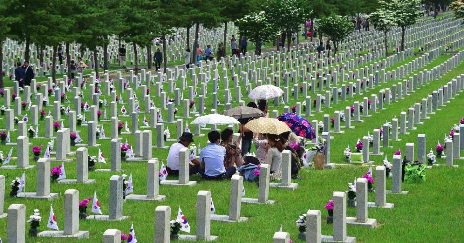6.jun.2016 - Família sul-coreana visita túmulo de vítima da Guerra da Coreia, durante cerimônia no Cemitério Nacional para celebrar o Dia da Memória Coreana, em Seul. Esta segunda-feira marca o 61º aniversário do Dia da Memória na Coreia do Sul - a homenagem foi criada para lembrar das vítimas do conflito que dividiu a península coreana, entre os anos de 1950 e 1953