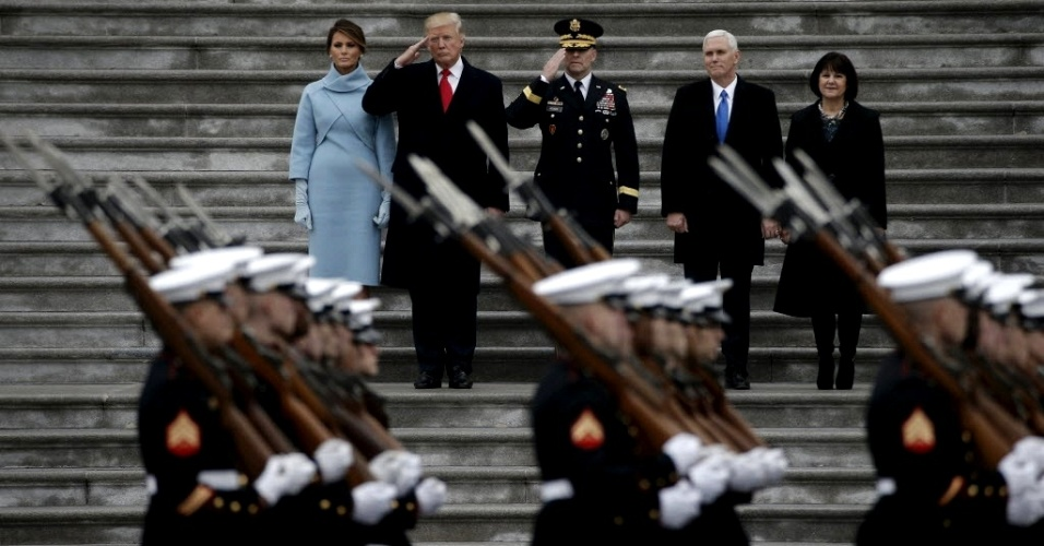 20.jan.2017 - Recém-empossado, o presidente dos EUA, Donald Trump (com gravata vermelha), sua mulher, Melania (à esquerda), o vice-presidente Mike Pence (com gravata azul) e sua mulher, Karen (à direita), observam desfile militar que faz parte da cerimônia de posse, em Washington DC, nesta sexta-feira (20)