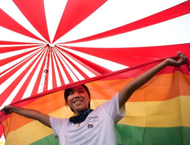 Vietnamita segura bandeira do arco-íris durante parada do orgulho gay, em Hanói