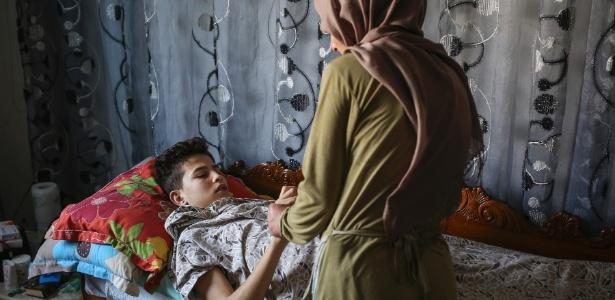 Aziz, 13, que ateou fogo a si mesmo, recebe cuidado da mãe em sua casa em Bou Hajla