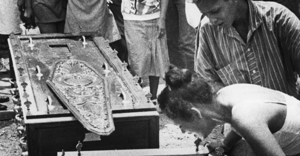 Valdivina Batista de Oliveira debruça-se sobre o caixão do sobrinho Israel Batista dos Santos, 22, morto em 27 de outubro de 1987, e chora, em Goiânia (GO); momentos depois desmaiaria
