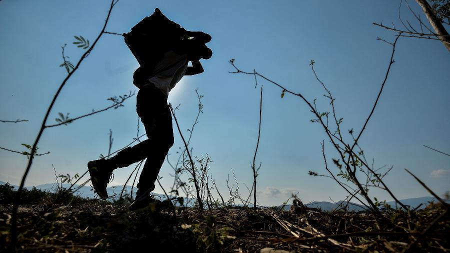 Homem tentar cruzar a fronteira entre a Venezuela e a Colômbia por trilha irregular - LUIS ROBAYO/AFP