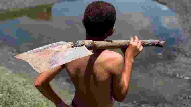 Criança trabalha em água poluida do rio Capibaribe, no Recife (PE) - Diego Herculano/Folhapress