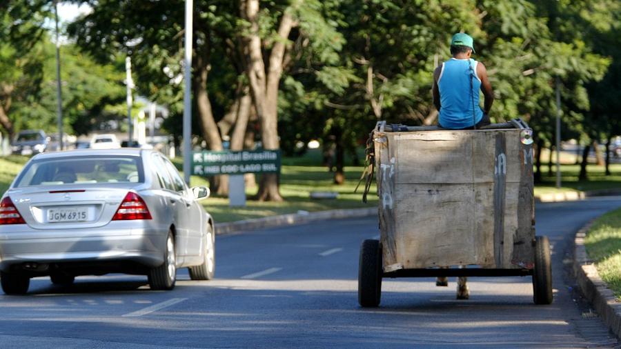 Carroceiro passa ao lado de uma Mercedes Benz, mostrando a desigualdade em bairro nobre de Brasília, em 2005 - Lula Marques/Folhapress