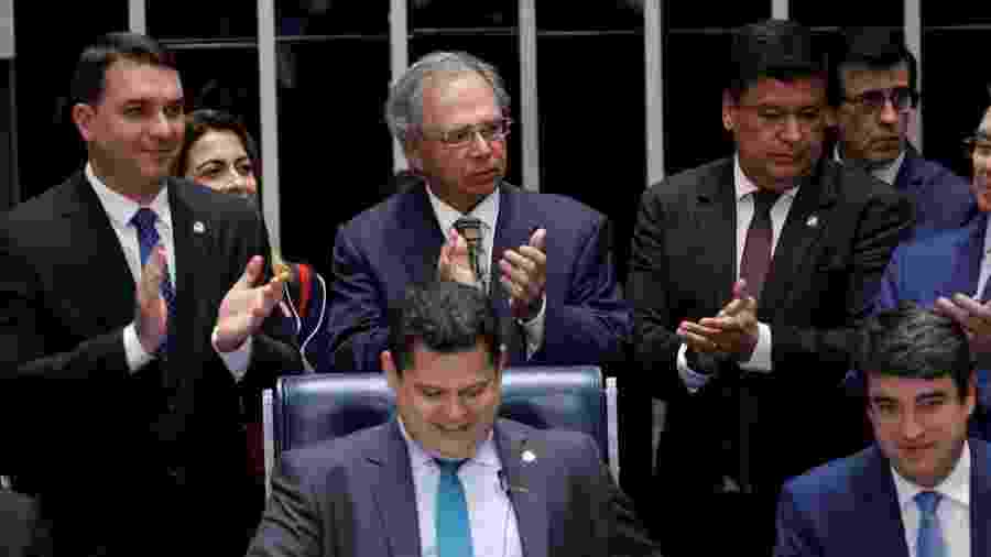 O senador Flávio Bolsonaro, o ministro Paulo Guedes (na foto, os dois à esquerda e em pé) e o presidente da Casa, Davi Alcolumbre (sentado, ao centro), entre outros, comemoram aprovação de texto-base no Senado - Adriano Machado/Reuters