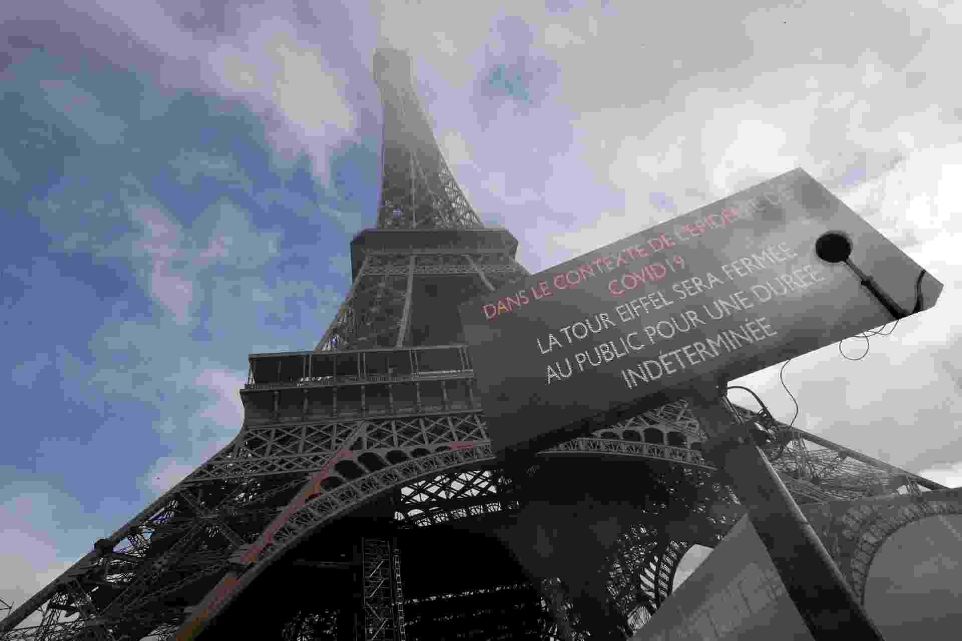 Imagem mostra placa em frente à torre Eiffel, um dos cartões-postais de Paris (França), alertando que visitas proibidas como medida de cautela em relação ao coronavírus - Thomas Samson/AFP