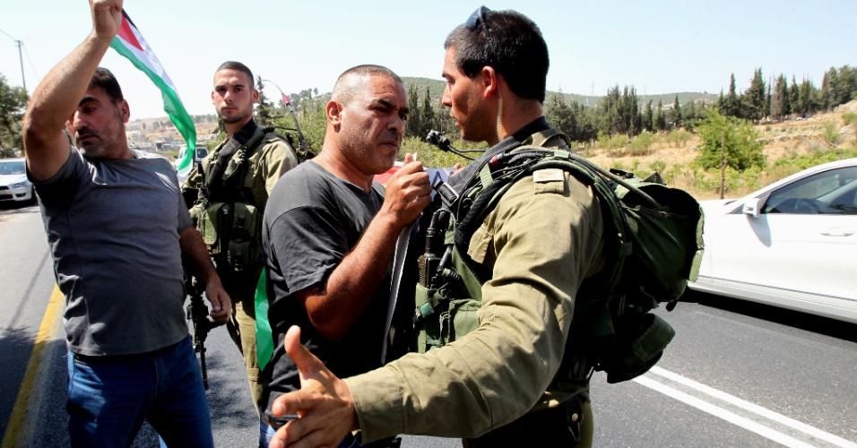 8.ago.2015 - Ativistas palestinos e estrangeiros confrontam soldados israelitas em estrada na Cisjordânia usada principalmente por colonos israelenses, ao norte da cidade de Hebron, neste sábado (8), durante manifestação para condenar o ataque com uma bomba incendiária na semana passada que causou a morte de um bebê palestino em Duma. Neste sábado, o pai da criança, que estava internado com 80% do corpo queimado, acabou morrendo. O ataque foi realizado por colonos judeus na Cisjordânia, ocupada por Israel