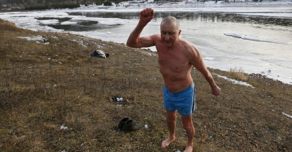 """6.jan.2015 - Vladimir Khokhlov, 71, integrante do clube Cryophile de nadadores de inverno, se aquece antes de se banhar na água gelada do rio Mana, em Krasnoyarsk, na Rússia. A temperatura no momento era de -5°C. """"Não posso viver sem me banhar diariamente em águas geladas. É como um vício"""", diz ele. """"Quando não estamos no inverno, tento encontrar outra forma de jogar água gelada sobre meu corpo da cabeça aos pés"""""""