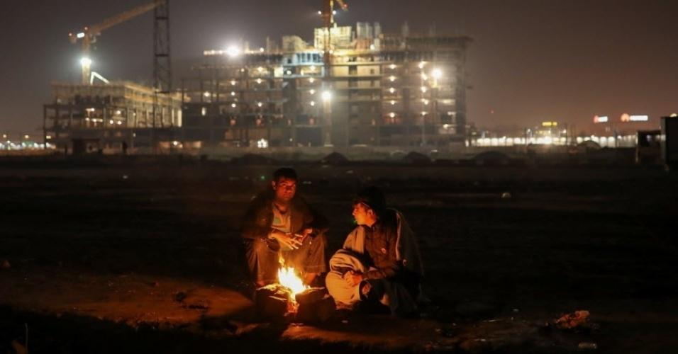 22.nov.2016 - Imigrantes se aquecem em volta de fogueira em armazém abandonado em Belgrado, na Sérvia