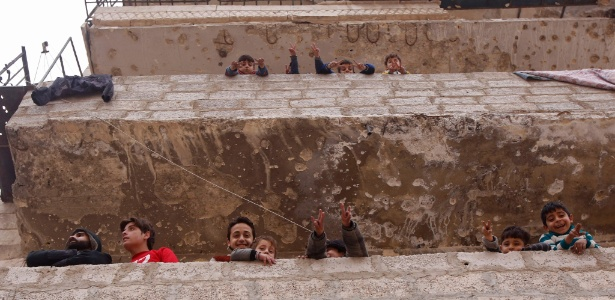 Moradores de uma área controlada pelo governo sírio em Aleppo
