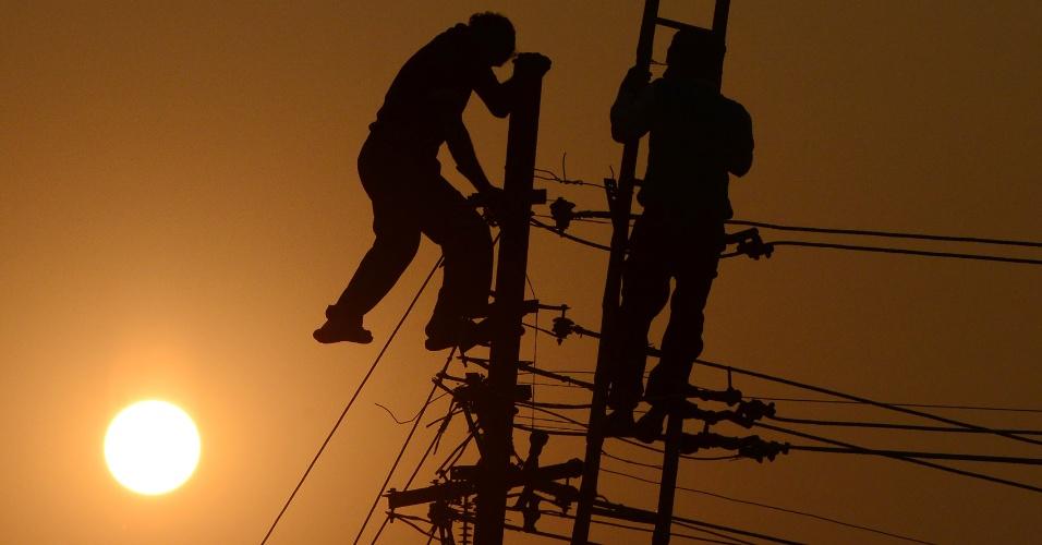 19.dez.2016 - Trabalhadores ajustar os cabos de electricidade sobre as margens do rio Ganges em Allahabad, na Índia
