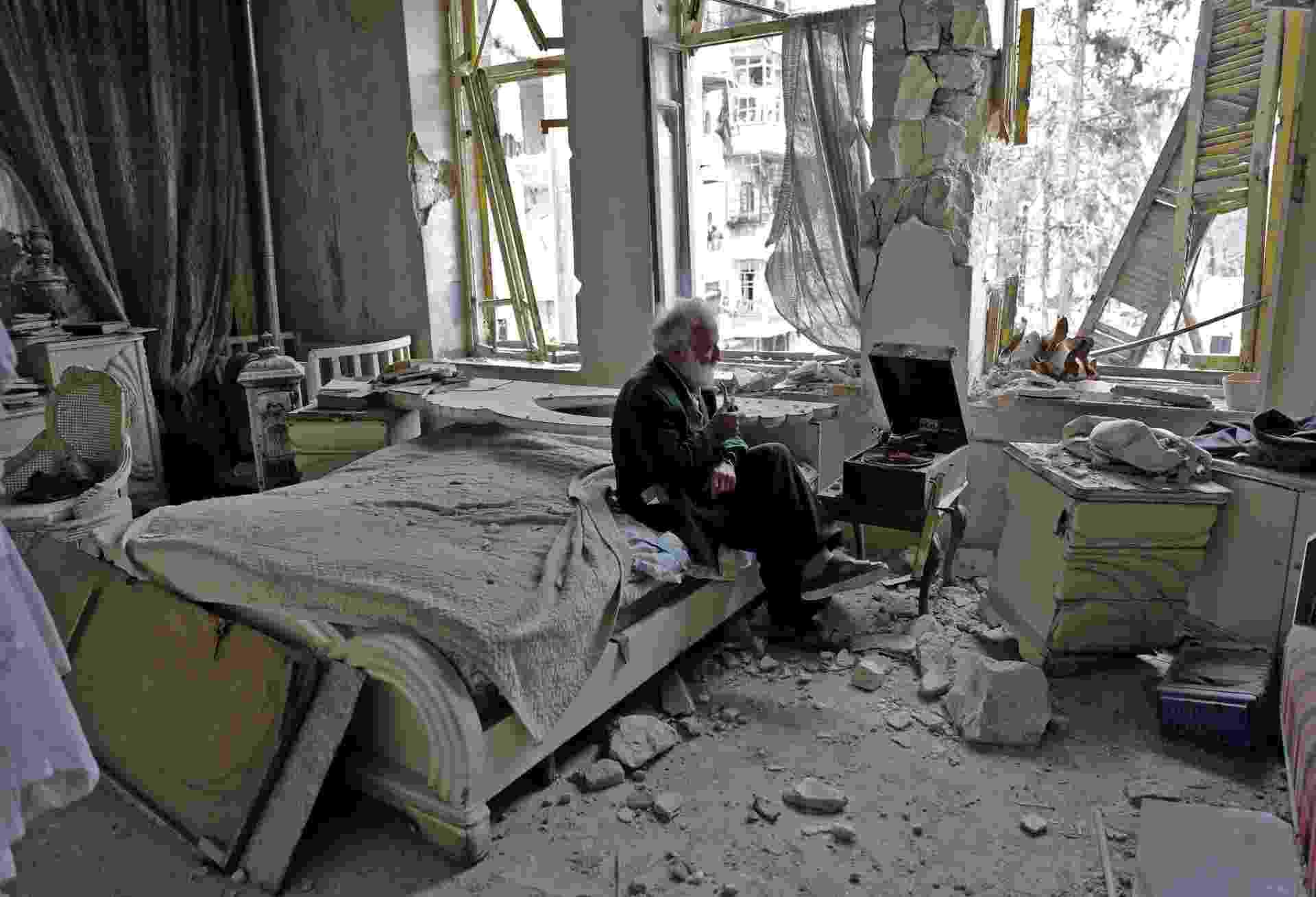 """Mohammad Mohiedine Anis, 70, fuma o seu cachimbo e ouve música em sua vitrola em seu quarto em Aleppo, na Síria. Conhecido na região pelo seu apelido, Abu Omar, o sírio é dono de uma coleção de carros antigos. O autor da imagem, Joseph Eid, conta que a foto foi tirada durante um tour pela casa em que Abu Omar ainda vive. """"Ele nos disse que ainda usava muito a vitrola, já que ela é mecânica e não depende de eletricidade para operar"""". O sírio colocou uma de suas músicas favoritas para tocar, Hekaya (História, em árabe), do cantor sírio Mohammad Dia al Din. - JOSEPH EID/AFP"""