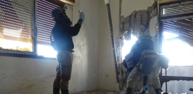29.ago.2013 - Especialistas em armas químicas da ONU (Organização das Nações Unidas) usam máscara contra gás enquanto verificam local de um suposto ataque de armas químicas, na Síria