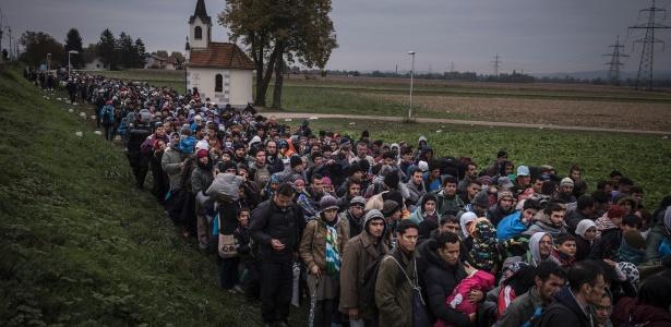 Refugiados são escoltados para campo de registro, nos arredores de Dobova, na Eslovênia