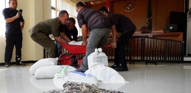Funcionários do Judiciário tailandês carregam pagamento de Dwi Susilarto a sua ex-mulher, Hermi Setyowati, após divórcio - Ganug Nugroho Adi/Jakarta Post