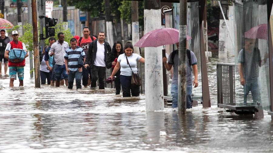 Pedestres passam por ponto de alagamento na Avenida Comendador Martinelli (Zona Norte de SP) - BRUNO ESCOLASTICO/ESTADÃO CONTEÚDO