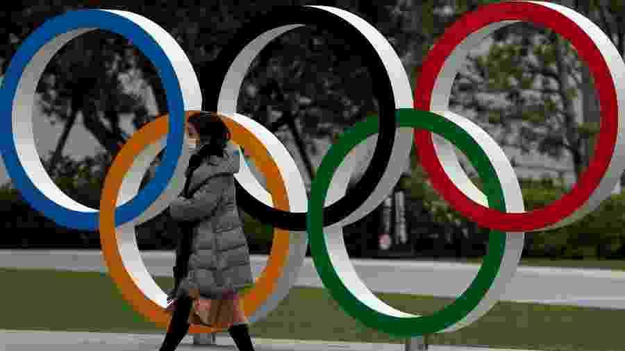 Pedestre caminha em frente a anéis olímpicos em Tóquio - Issei Kato