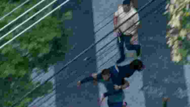 30.mai.2020 - O comerciante Rafael Presta, anfitrião da festa clandestina e aniversariante, carrega a médica Ticyana Azambuja nas costas. Um outro homem de camisa amarela segura o martelo usado por ela para quebrar o retrovisor e o vidro traseiro do carro do PM - Reprodução - Reprodução
