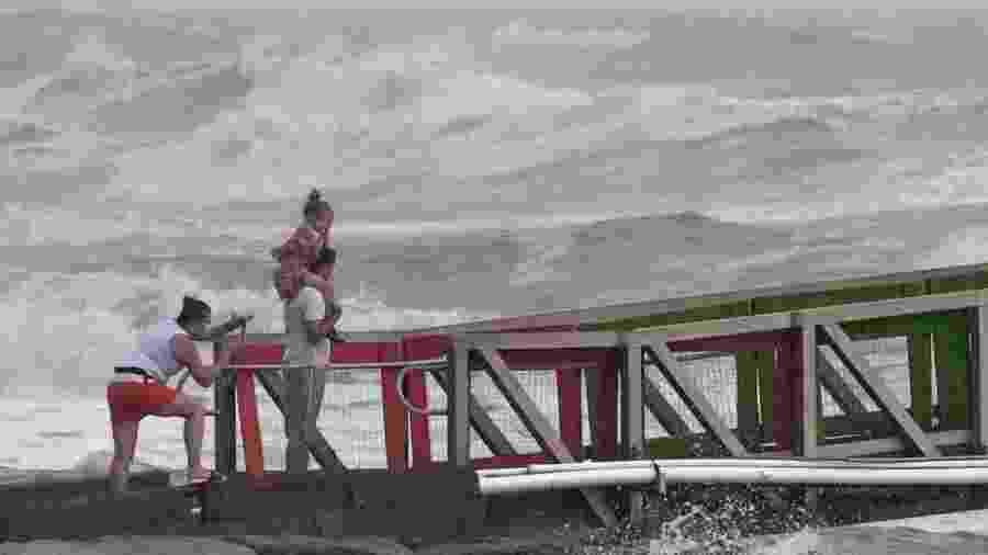 Menina protege o rosto dos ventos fortes, enquanto a família assiste a altas ondas do furacão Hanna de um cais em Galveston, Texas, EUA - ADREES LATIF/REUTERS