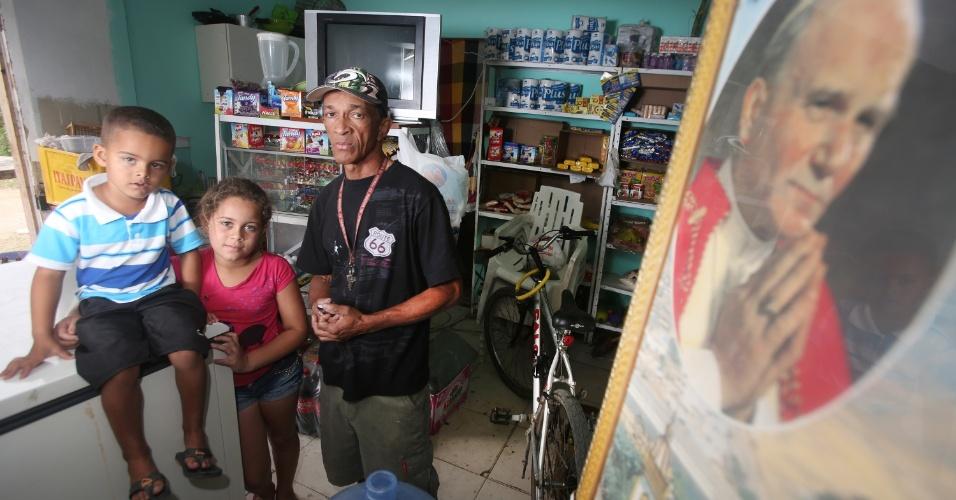 6.jul.2015 - Ao lado dos dois netos, o comerciante Lauro Luís dos Santos, 52, conta que teve prejuízo de cerca de R$ 1.000 após pegar R$ 3.000 emprestados para investir na vendinha, em 2013, antes de os atos no Campus Fidei, em Guaratiba, na zona oeste do Rio de Janeiro, serem cancelados