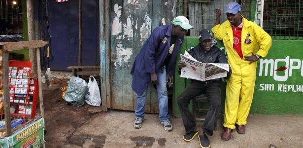 Homens, no bairro de Kibera, em Nairóbi, leem matéria de jornal - Till Muellenmeister/AFP