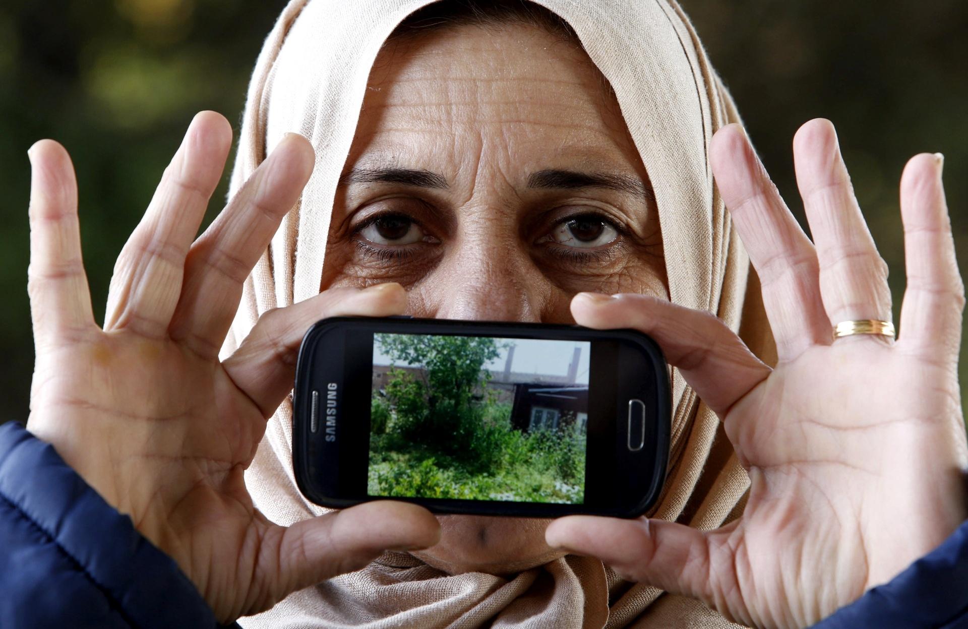 Logine, de Hamslo, na Síria, mostra uma imagem de sua casa enquanto aguarda para cruzar a fronteira da Eslovênia com a Áustria