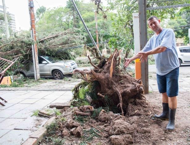 Dono de um comércio em um estacionamento, Amarildo Back, teve seu carro destruído (ao fundo), além do prejúizo com outros carros e seu comércio - UOL