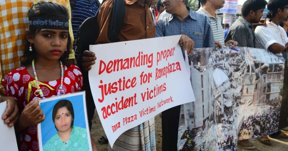 24.abr.2016 - Em Dhaka, capital de Bangladesh, criança segura cartaz com foto de sua mãe, uma das vítimas do desabamento de um prédio comercial na cidade que resultou na morte de mais de 1.100 pessoas há três anos. Milhares de manifestantes foram às ruas da cidade pedir justiça e melhores condições de trabalho no país