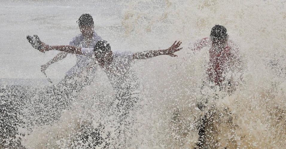 23.jun.2016 - Meninos brincam em meio as ondas de uma maré alta, em Mumbai, Índia. As chuvas de monções, que acontecem de junho a setembro, já cobriram quase metade do país
