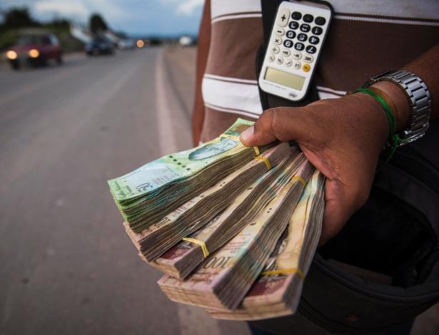 Cambista brasileiro troca bolívares por reais na entrada para a cidade venezuelana Santa Elena Uairén, que faz divisa com Pacairama (RR)