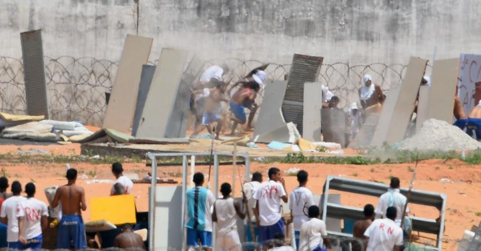 17.jan.2016 - Detentos se protegem com pedaços de madeira dos disparos de bala de borracha feitos pela polícia na Penitenciária Estadual de Alcaçuz