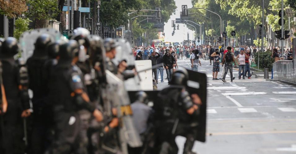 9.fev.2017 - Policiais militares e manifestantes com o rosto coberto ficam frente a frente na avenida Rio Branco, uma das principais do centro do Rio, durante confronto nas imediações da Alerj