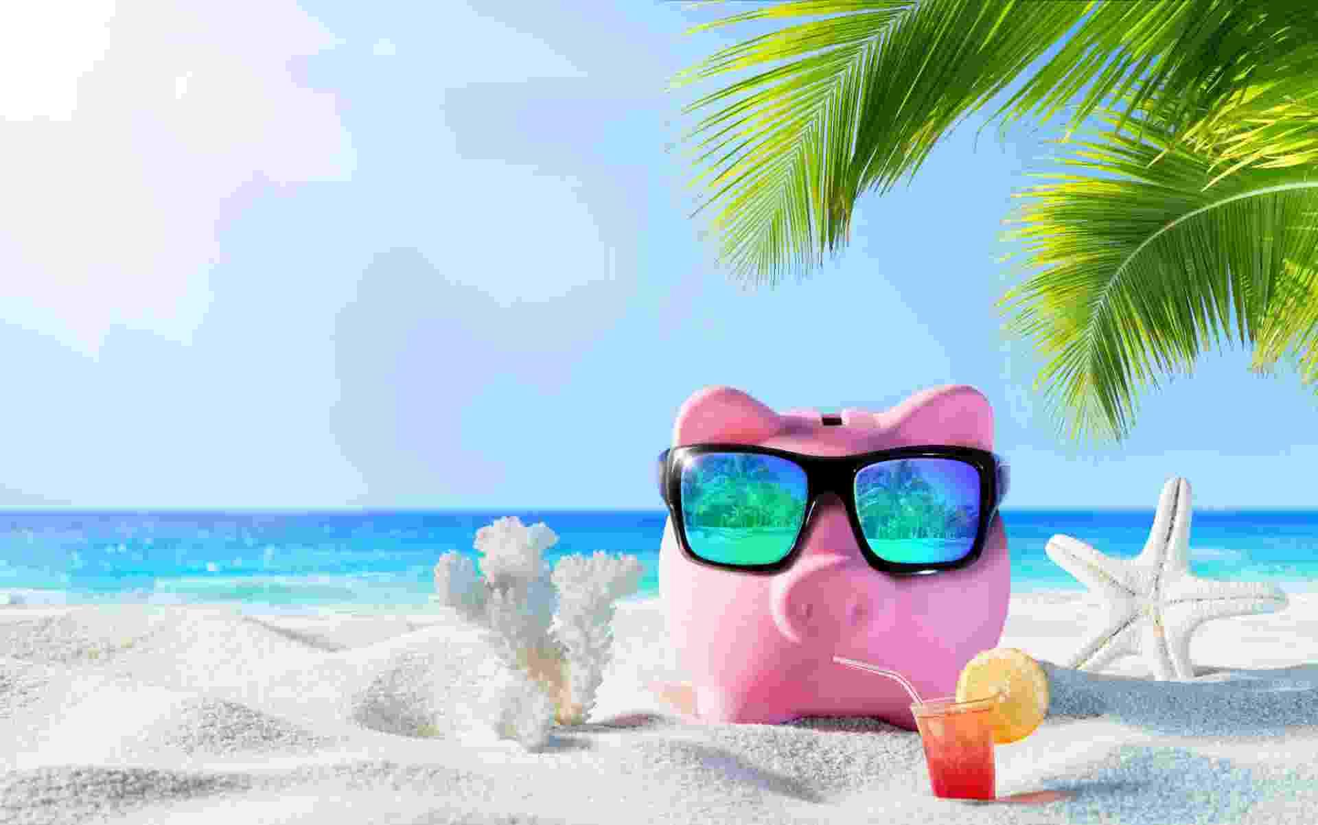 Porquinho na praia, dinheiro, férias, finanças - Getty Images/iStockphoto/RomoloTavani