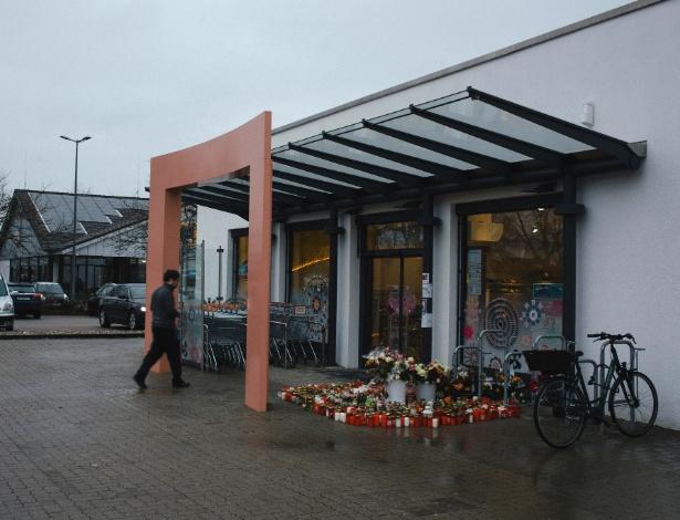 Cidadãos colocam flores e velas na entrada da farmácia onde uma adolescente foi morta em Kandel, na Alemanha