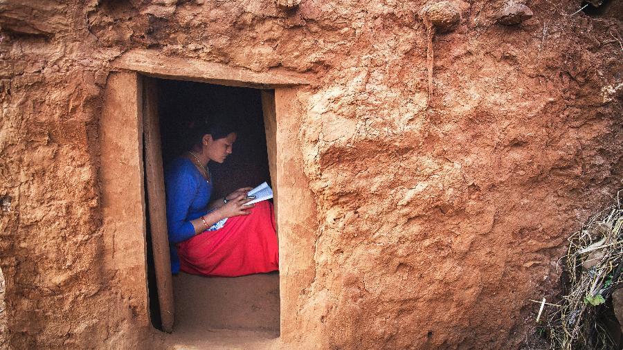 Kusum Thapa, 17, faz lição de casa na Chhaupadi de sua família, na aldeia de Dhungani, Nepal - Tara Todras-Whitehill/The New York Times