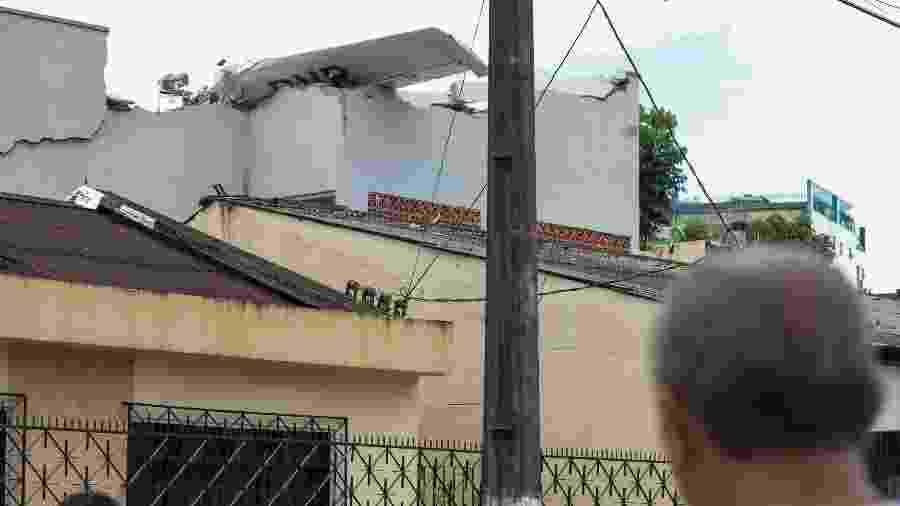 Morador observa destroços de avião de pequeno porte que caiu sobre casa em região residencial de Belém logo após a decolagem - Filipe Bispo/ Foto Arena/Estadão Conteúdo
