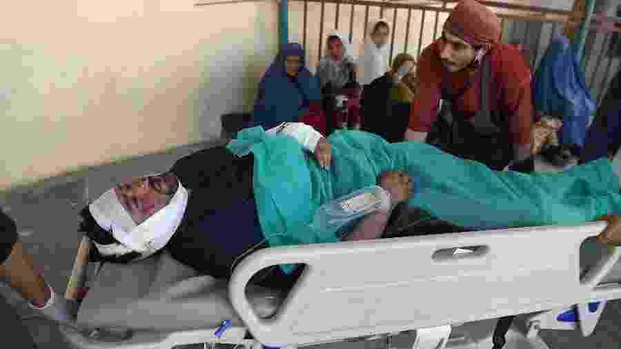 Um homem ferido é levado ao hospital após um atentado próximo a um comício do presidente do Afeganistão, Ashraf Ghani - Wakil Kohsar/AFP