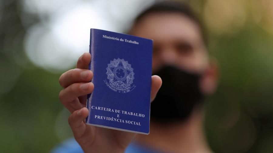 Homem mostra carteira de trabalho enquanto procura por oportunidades de emprego no centro de São Paulo - Amanda Perobelli/Reuters