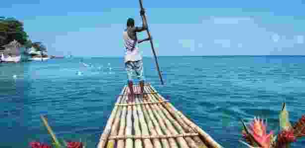 14.mar.2016 - O crescimento jamaicano. Um guia empurra uma canoa de bambu pela praia de Porto Antonio, na Jamaica. O turismo é responsável por boa parte da economia do país: cerca de 10% dos empregos e 27% do PIB - Shannon Hibberd/National Geographic Creative - Shannon Hibberd/National Geographic Creative